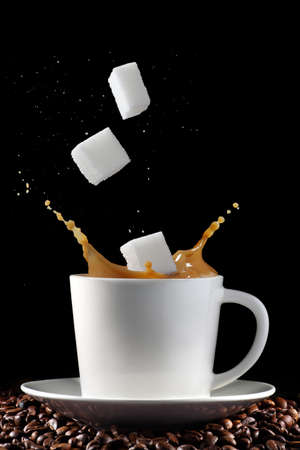 sugar cubes: Cup of coffee with splash and sugar cubes