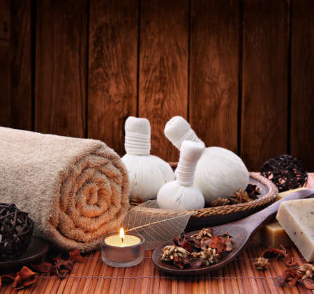 day spa: Candlelight spa setting with thai herbal compress massage stamps Stock Photo