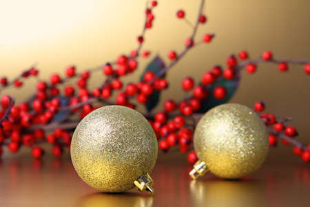 Golden christmas baubles and red berry garland    photo