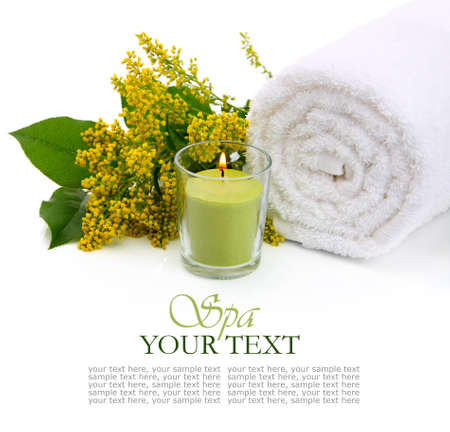 rejuvenate: Spa setting with rolled towel, flowers and burning candle