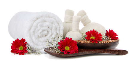 Spa massage setting with rolled towel and flowers photo