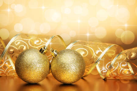 Christmas ornaments with curled ribbon on golden holiday background photo