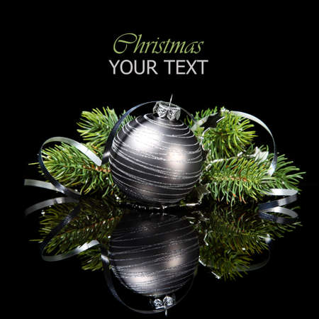 Christmas ornament with pine tree branches on a black background