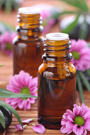 Aromatherapy bottles with pink flowers photo