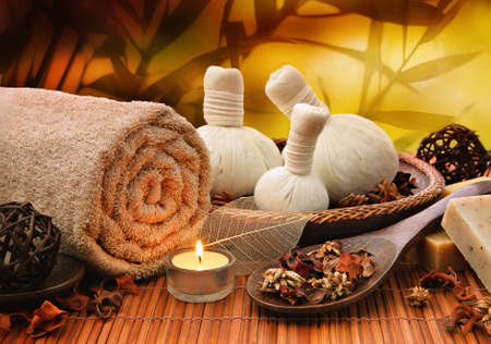natural setting: Spa setting with a rolled towel, massage balls and candlelight Stock Photo