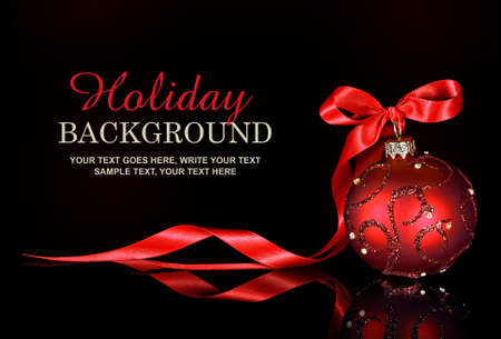 Christmas background with a red ornament and ribbon on a black background