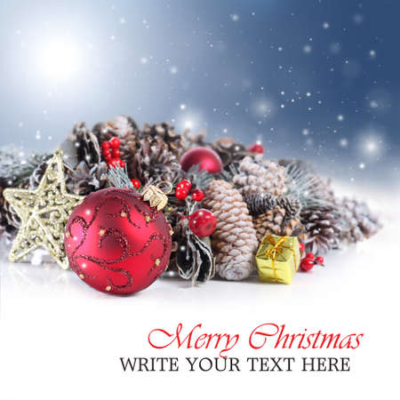 Christmas or holiday background with red ornament, garland and snowflakes falling from a blue sky Standard-Bild