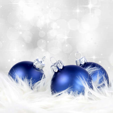 Christmas or holiday background with blue silver ornaments on billowy feathers