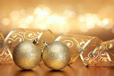 Christmas or holiday background with two golden ornaments, ribbon and bokeh