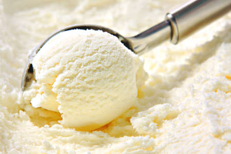 ice cream scoop: Vanilla ice cream scoop scooped out of container with untensil