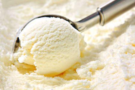 Vanille-ijs scoop uitgehold van de container met untensil Stockfoto