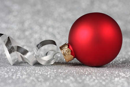 Red Christmas ornament with curled ribbon on a silver background Standard-Bild