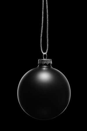 Hanging black Christmas ornament on a black background. Low key. Stock Photo