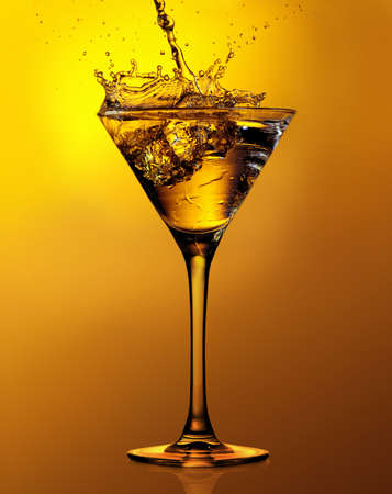 Martini cocktail with splash against a gold background 版權商用圖片