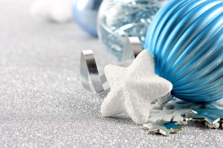 Holiday background with white snowflake and blue Christmas ornaments