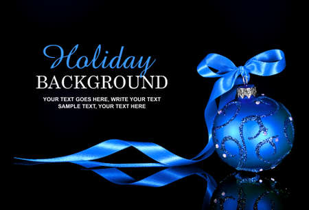 Holiday background with blue Christmas ornament and ribbon
