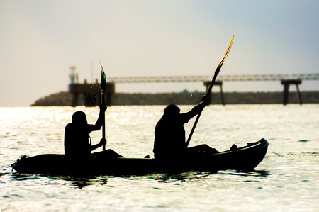 Silhouettes two people rowing on a sea photo