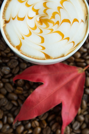 Latte art, close up of a beautiful cup of hot coffee and maple leaves. photo
