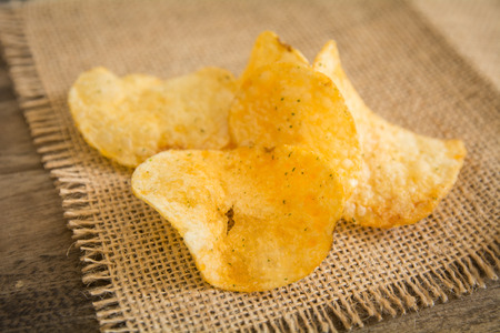 Crispy potato chips on wooden background