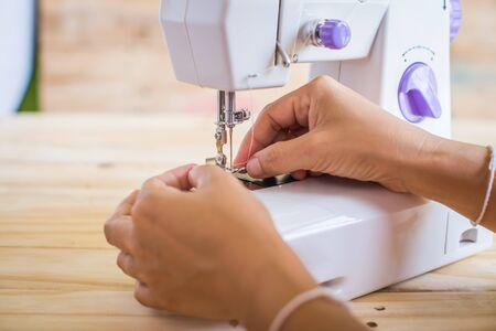 women's hands: Sewing Process - Womens hands behind her sewing
