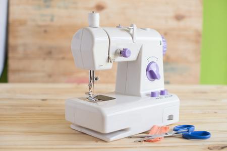 maquinas de coser: M�quina de coser moderna en la mesa de madera Foto de archivo