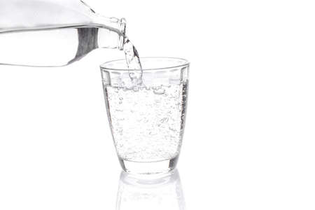 carbonated drink: Transparent carbonated drink poured into a transparent container, shot on white background. Stock Photo