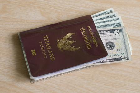wooden insert: Dollar money insert in Thai passport put on wooden floor Stock Photo