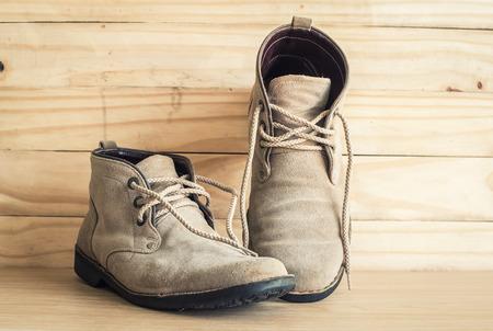 men s feet: Brown shoe on old wood background, still life.