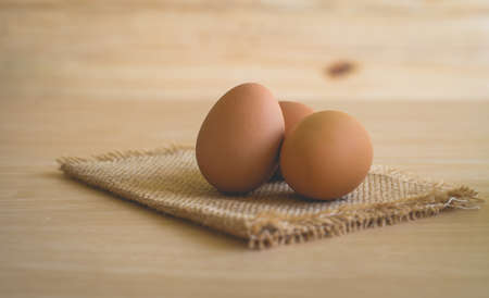 gunny: Some brown eggs on a sackcloth on a wooden table.