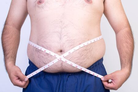 measure waist: Fat man trying to measure waist circumference