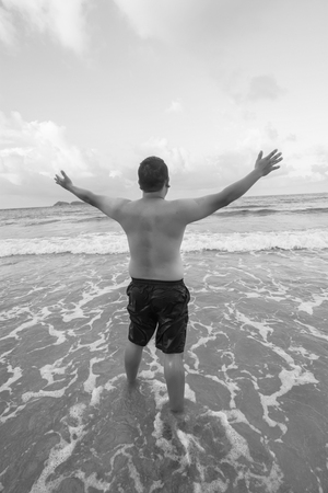 greatness: Mature man with open arms at the beach praising the greatness of a higher power. Black-white photo