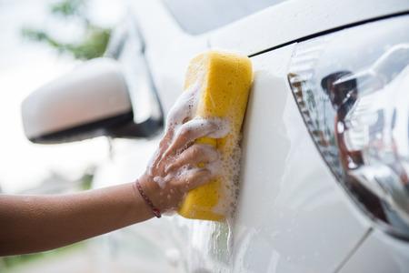 women washing car with yellow sponge