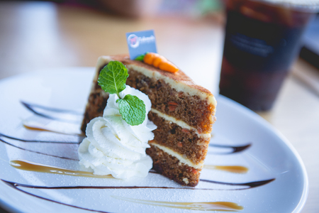 Cake having carrot is a mixture and decorated with whipped cream,caramel,mint leaves on white plate color.