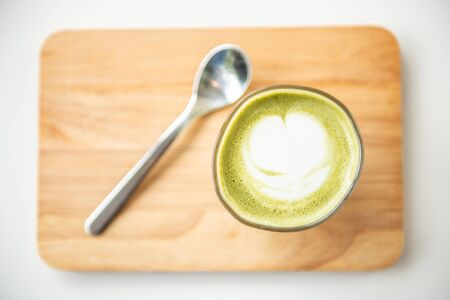 Hot green tea latte with spoon on wooden plate Stock Photo