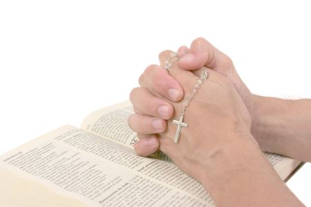 Hands over Bible praying