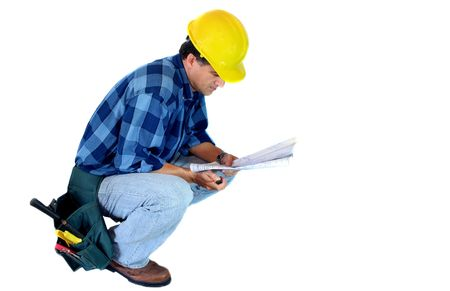 Builder kneeling reading a Blueprint
