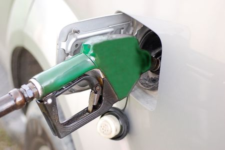 Green refueling hose inside a cars fuel tank Stock Photo