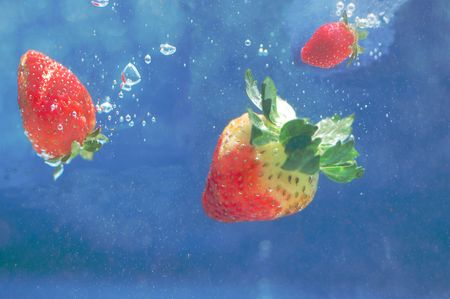 Strawberries falling in deep blue water photo