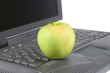 A green apple on top of a laptop photo