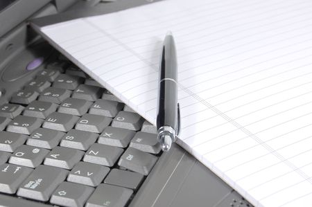 Notepad and pen on the keyboard of a laptop Stock Photo