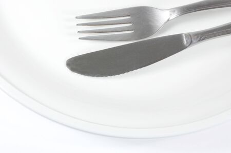 Knife and fork on a plate isolated on white Stock Photo