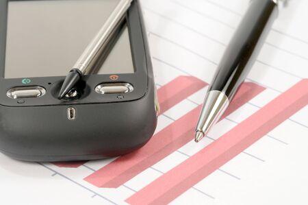 cel: Telefono cel su un grafico di affari con una penna a fianco