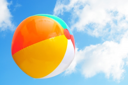 Colorful beach ball up in the air with beautiful blue sky