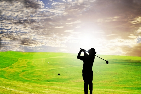 Silhouette of a golfer against the early morning sky and sun