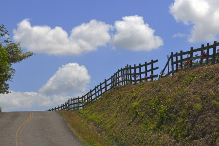 Panoramic shot of a mountain road with a fence and a blue sky photo