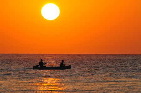 Silhouette of a two men on a boat at sunrise out of the coast of Corona Beach, Panama.