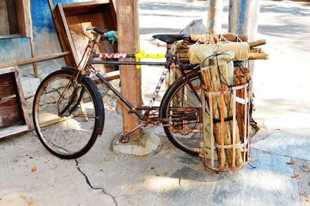 bycicle: Old bike parked at a porch at a street in Asia. Stock Photo