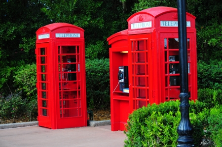 Three red british  phone booths  at a street photo