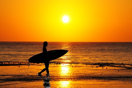 Surfer silhouette walking into the waves at sunrise Stock Photo