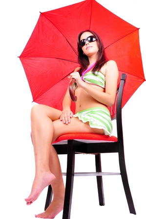 sun umbrella: Beautiful young woman on a bathing suit sitting holding a red umbrella Stock Photo